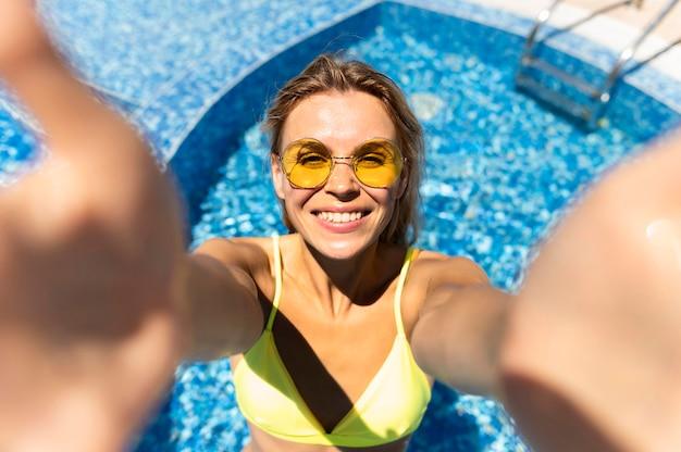 Mulher sorridente tomando selfie na piscina