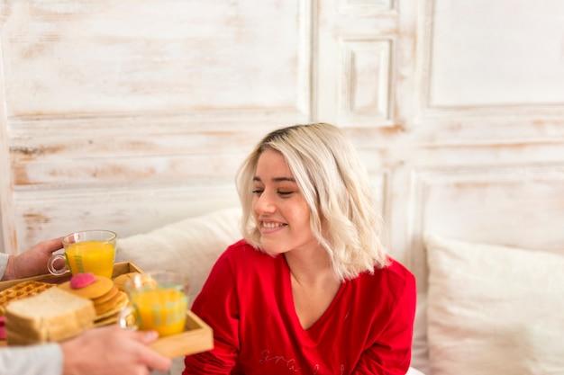 Mulher sorridente, tomando seu café da manhã na cama