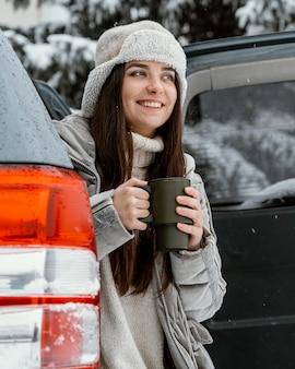 Mulher sorridente tomando uma bebida quente durante uma viagem