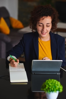 Mulher sorridente, trabalhando à distância usando um tablet digital enquanto faz anotações
