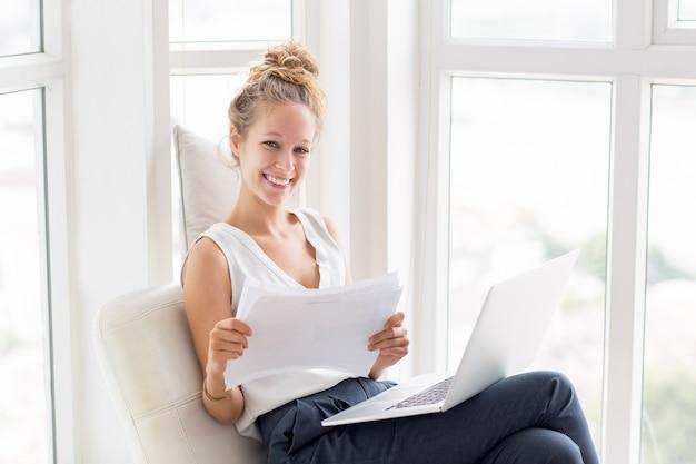 Mulher sorridente trabalhando com documentos no windows
