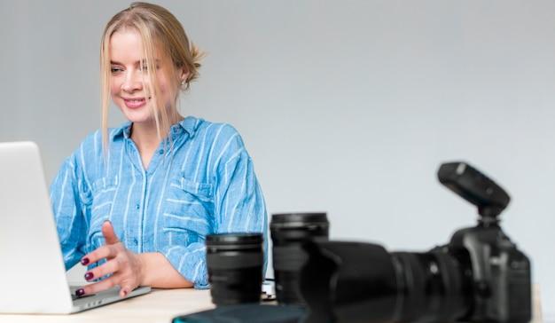 Mulher sorridente, trabalhando em seu laptop e câmera com lente