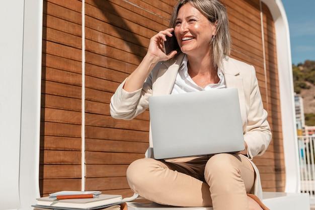Mulher sorridente trabalhando em um laptop