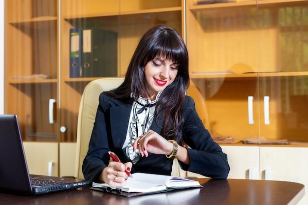 Mulher sorridente, trabalhando no escritório e olhando para o relógio