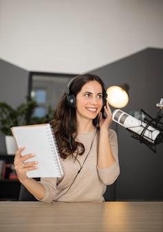 Mulher sorridente transmitindo no rádio