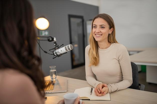Mulher sorridente transmitindo uma entrevista no rádio