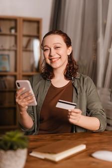 Mulher sorridente usando cartão de crédito e smartphone em casa
