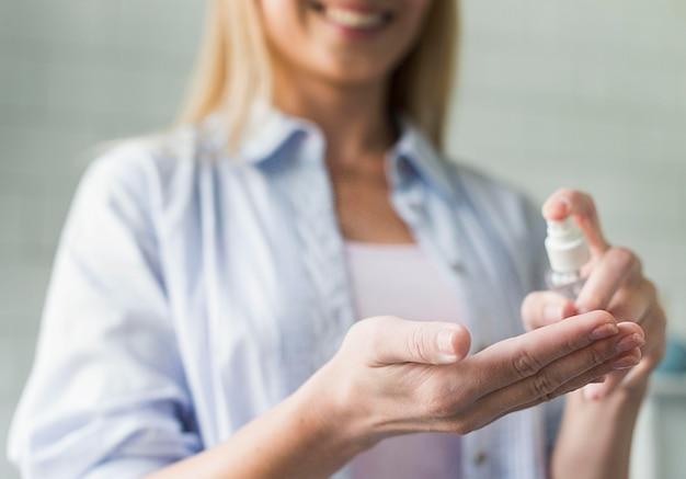 Mulher sorridente usando desinfetante para as mãos