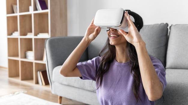 Mulher sorridente usando fone de ouvido de realidade virtual em casa