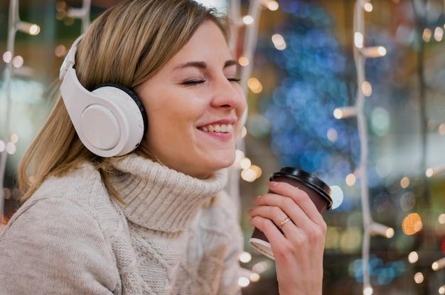 Mulher sorridente, usando, fones segurando, copo, luzes natal