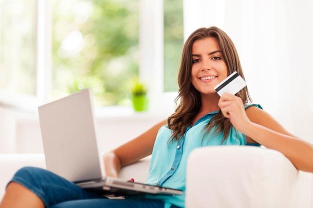 Mulher sorridente usando laptop e segurando um cartão de crédito