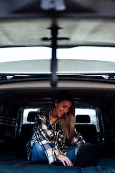 Mulher sorridente usando laptop enquanto estava deitada na cama na van
