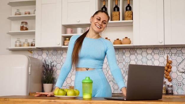 Mulher sorridente usando o computador no interior da cozinha moderna. cozinhar e conceito de estilo de vida saudável. mulher transmite online e gesticula emocionalmente