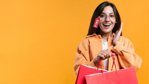 Mulher sorridente usando óculos com etiqueta de venda e segurando sacolas de compras