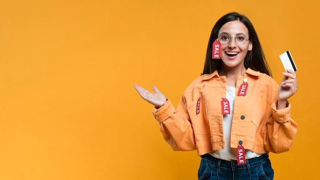 Mulher sorridente usando óculos com etiqueta de venda e segurando um cartão de crédito