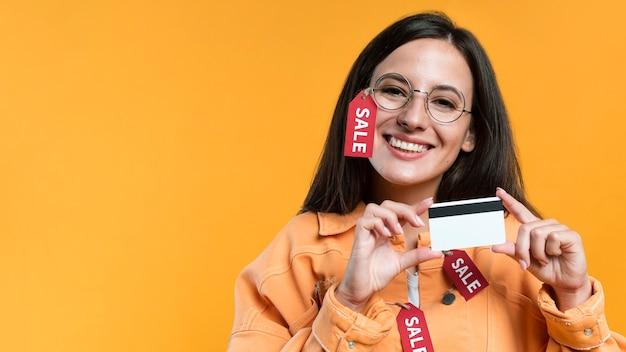 Mulher sorridente usando óculos e jaqueta com etiqueta de venda e segurando um cartão de crédito