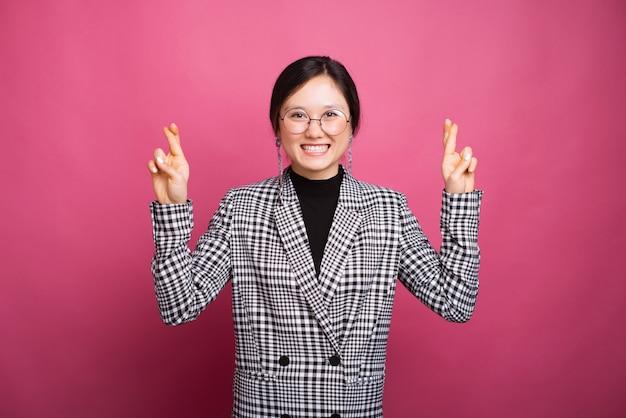 Mulher sorridente usando óculos está fazendo gesto de esperança, cruzando os dedos.