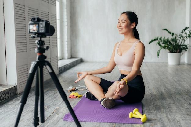 Mulher sorridente usando roupas esportivas fazendo vlogs enquanto medita