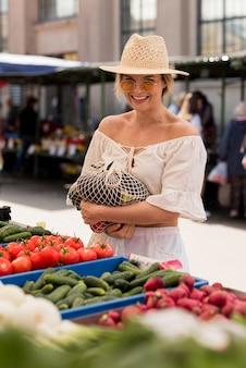 Mulher sorridente usando saco orgânico para vegetais