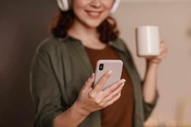 Mulher sorridente usando seu smartphone com fones de ouvido em casa enquanto toma café