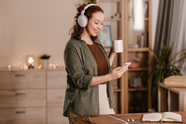 Mulher sorridente usando smartphone e fones de ouvido em casa enquanto toma um café