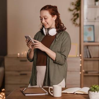 Mulher sorridente usando smartphone e fones de ouvido em casa