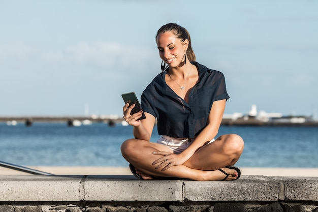 Mulher sorridente usando smartphone em aterro no verão