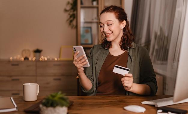 Mulher sorridente usando smartphone em casa com cartão de crédito