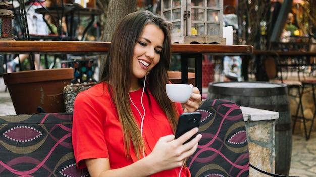 Mulher sorridente, usando, smartphone, enquanto, bebendo, xícara café