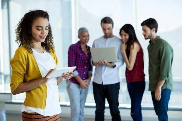 Mulher sorridente usando tablet digital no escritório enquanto um colega discute em segundo plano