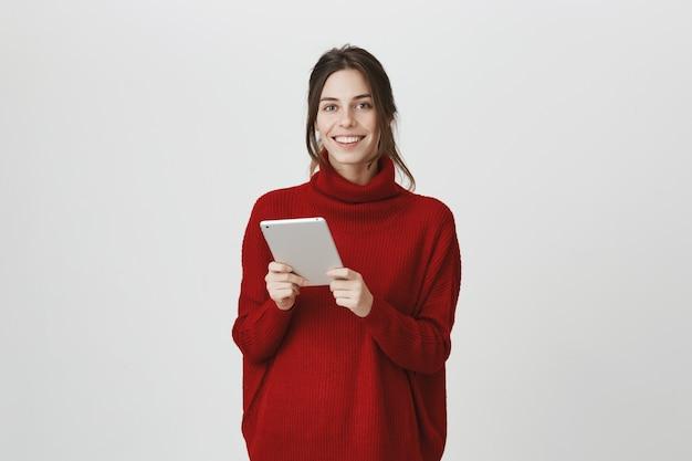 Mulher sorridente usando tablet digital Foto gratuita