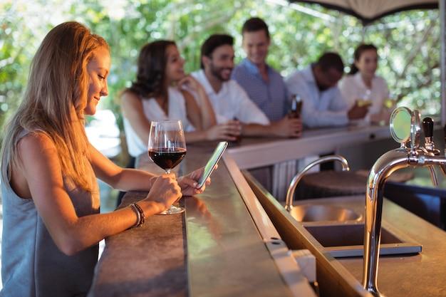 Mulher sorridente usando telefone celular enquanto toma uma taça de vinho