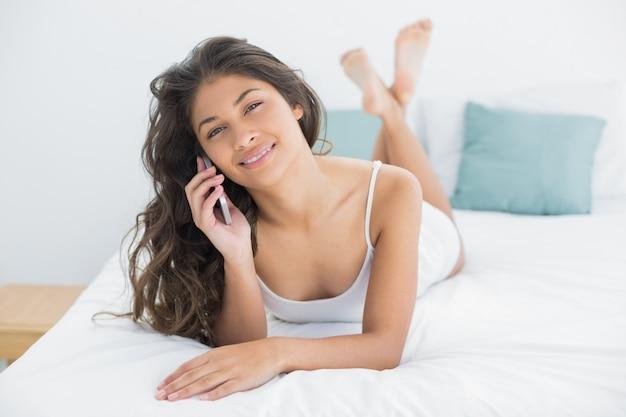 Mulher sorridente, usando, telefone móvel, cama
