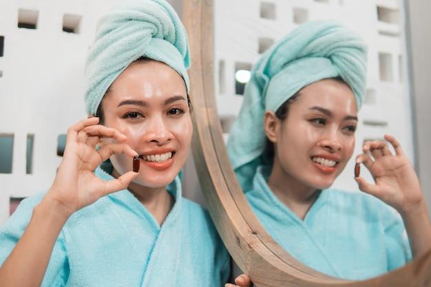 Mulher sorridente, usando toalha, tomando comprimido com vitamina e para nutrição, pele saudável em frente ao espelho