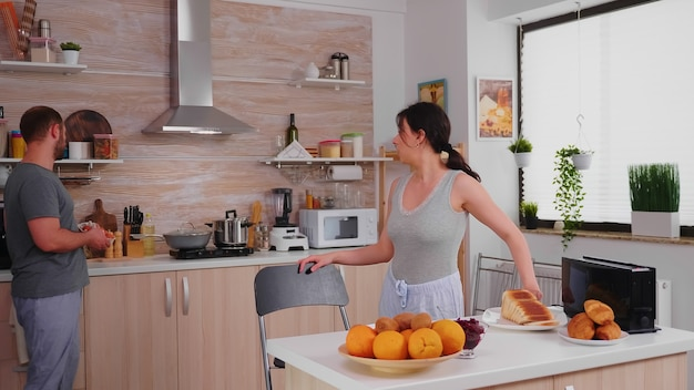 Mulher sorridente usando torradeira elétrica para fazer pão torrado no café da manhã. dona de casa usando torradeira elétrica para fazer pão torrado, além de um delicioso café da manhã para ela e o marido