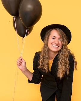 Mulher sorridente usando um chapéu e segurando balões