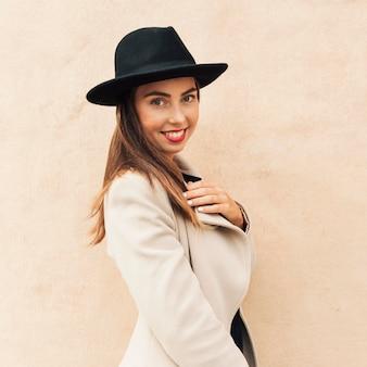 Mulher sorridente usando um chapéu preto
