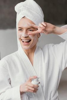 Mulher sorridente usando um creme facial branco