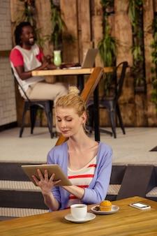 Mulher sorridente usando um tablet