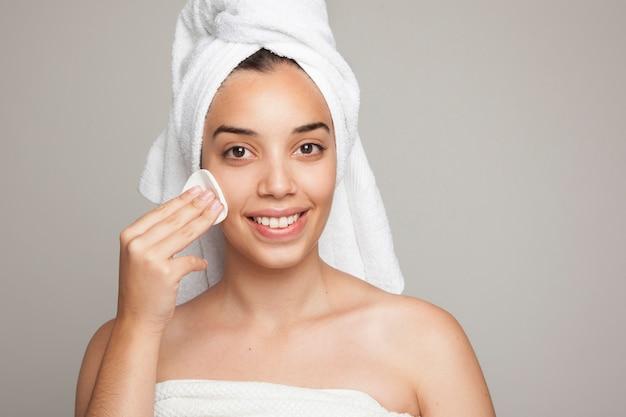 Mulher sorridente usando uma almofada de algodão no rosto
