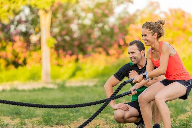 Mulher sorridente usando uma corda de batalha no parque e malhando com seu personal trainer.