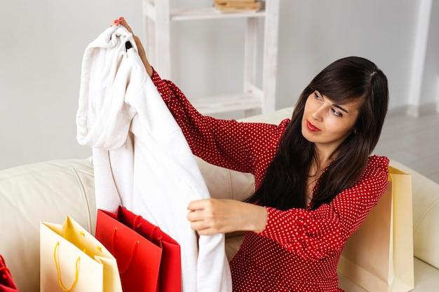 Mulher sorridente verificando as roupas que recebeu durante as compras
