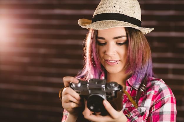 Mulher sorridente, verificando fotos da câmera vintage