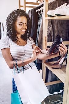 Mulher sorridente, verificando os saltos elegantes na loja