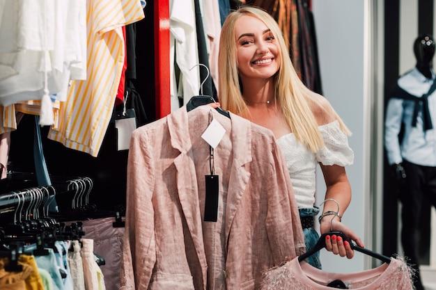 Mulher sorridente, verificando roupas