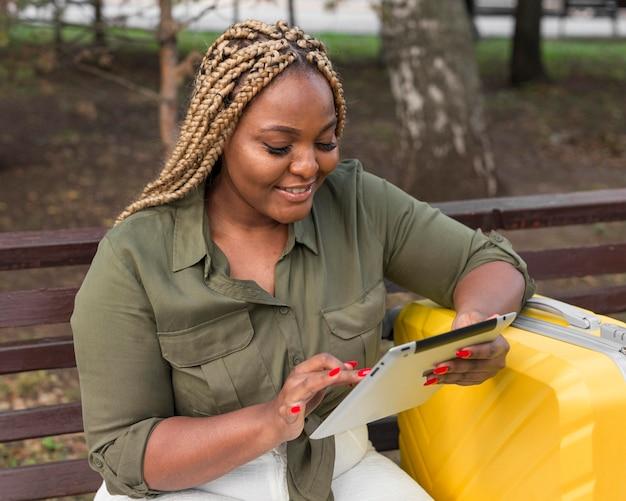 Mulher sorridente verificando seus aplicativos de mídia social no tablet