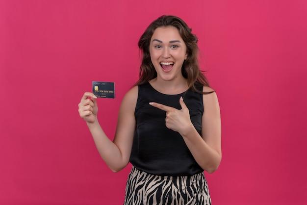 Mulher sorridente, vestindo camiseta preta, segurando um cartão do banco e apontando o cartão do banco na parede rosa