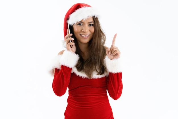 Mulher sorridente vestindo traje de natal e apontando para cima