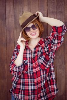 Mulher sorridente, vestindo um chapéu mole e óculos de sol