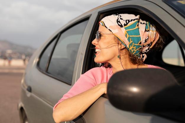 Mulher sorridente viajando de carro de perto